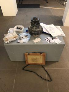 Auf einem Podest steht eine Nachbildung einer Urne in Menschenform, umgeben von Formularen und Tütchen mit Objekten. Am Podest lehnt ein Zeichenbrett.