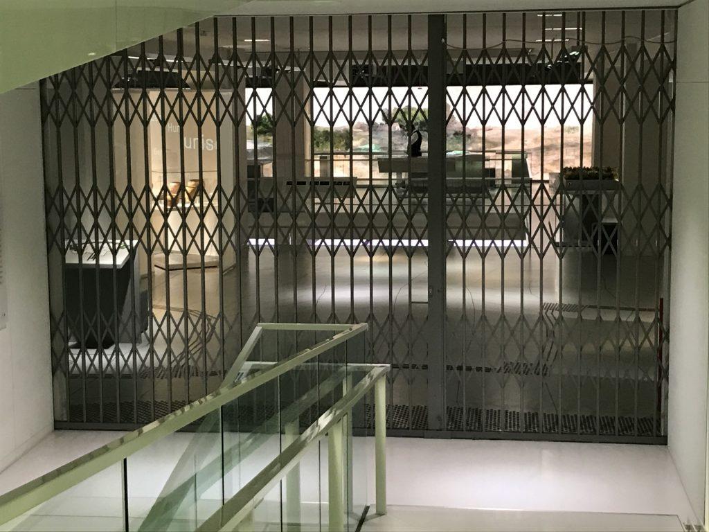 Geschlossene Gittertür, durch die Ausstellungsräume zu sehen sind.